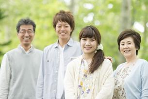 新緑の中で微笑む家族の写真素材 [FYI04548287]