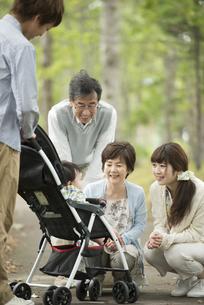 ベビーカーに乗る赤ちゃんに微笑みかける家族の写真素材 [FYI04548292]