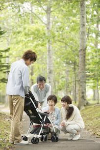 ベビーカーに乗る赤ちゃんに微笑みかける家族の写真素材 [FYI04548294]
