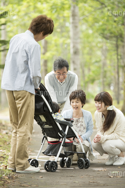 ベビーカーに乗る赤ちゃんに微笑みかける家族の写真素材 [FYI04548295]