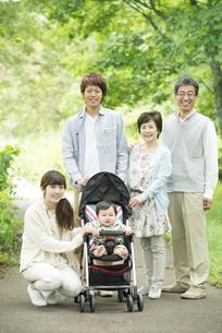 新緑の中で微笑む3世代家族の写真素材 [FYI04548297]