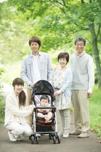 新緑の中で微笑む3世代家族の写真素材 [FYI04548298]