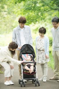 新緑の中で散歩をする3世代家族の写真素材 [FYI04548299]