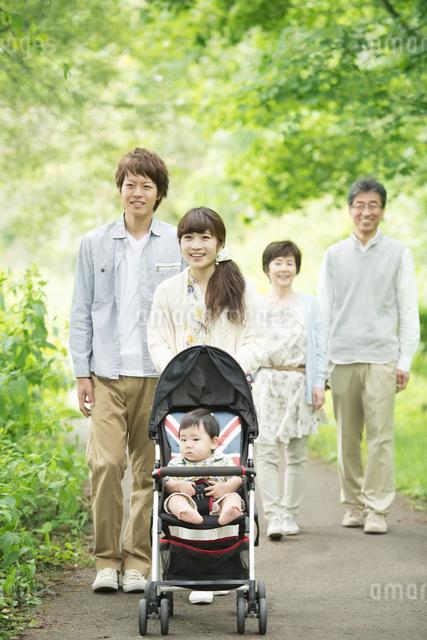 新緑の中で散歩をする3世代家族の写真素材 [FYI04548301]