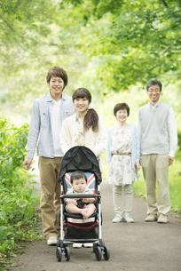 新緑の中で散歩をする3世代家族の写真素材 [FYI04548302]
