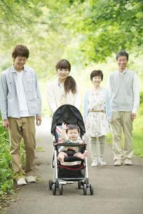 新緑の中で散歩をする3世代家族の写真素材 [FYI04548305]