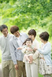 新緑の中で微笑む3世代家族の写真素材 [FYI04548313]
