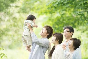 新緑の中で微笑む3世代家族の写真素材 [FYI04548318]