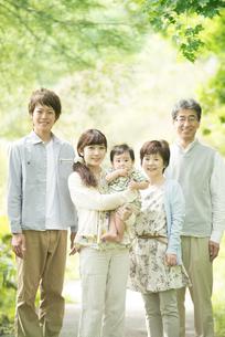 新緑の中で微笑む3世代家族の写真素材 [FYI04548329]
