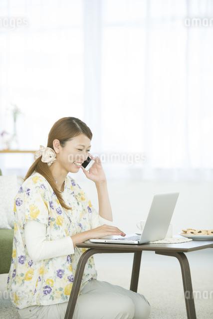 スマートフォンで電話をする女性の写真素材 [FYI04548357]