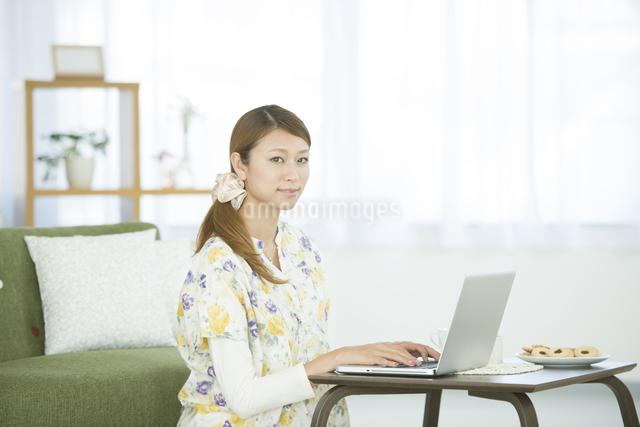 リビングでパソコン操作をする女性の写真素材 [FYI04548359]