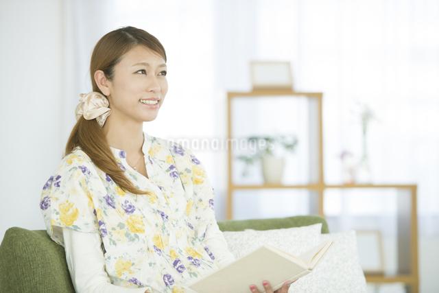 リビングで本を読む女性の写真素材 [FYI04548361]