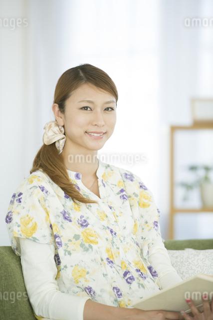 リビングで本を読む女性の写真素材 [FYI04548363]