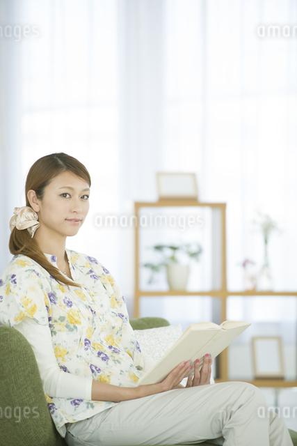 リビングで本を読む女性の写真素材 [FYI04548366]