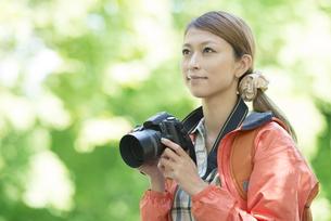 カメラを持ち微笑む女性の写真素材 [FYI04548370]