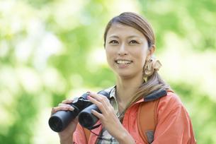 双眼鏡を持ち微笑む女性の写真素材 [FYI04548377]