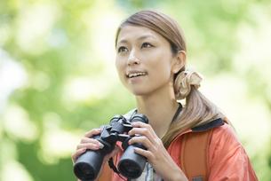 双眼鏡を持ち微笑む女性の写真素材 [FYI04548378]