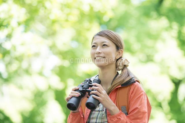 双眼鏡を持ち微笑む女性の写真素材 [FYI04548379]