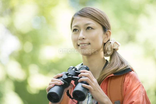 双眼鏡を持ち微笑む女性の写真素材 [FYI04548380]
