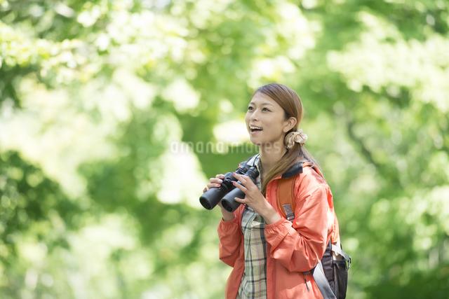 双眼鏡を持ち微笑む女性の写真素材 [FYI04548381]