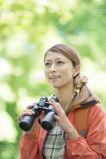 双眼鏡を持ち微笑む女性の写真素材 [FYI04548382]