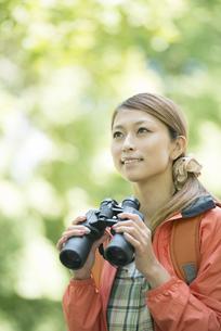 双眼鏡を持ち微笑む女性の写真素材 [FYI04548383]