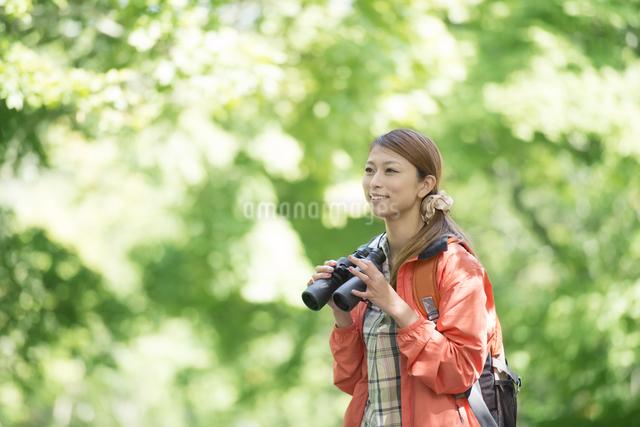 双眼鏡を持ち微笑む女性の写真素材 [FYI04548384]