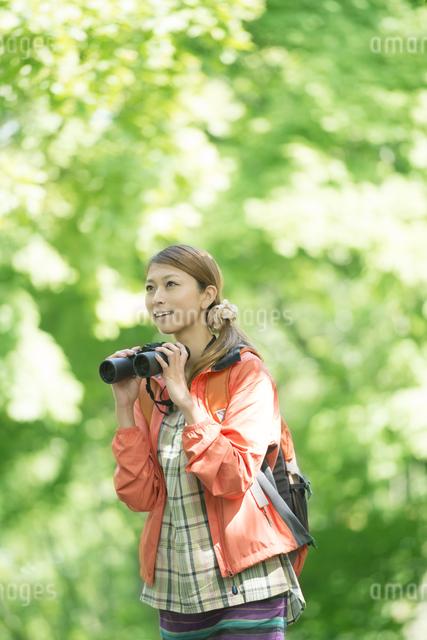 双眼鏡を持ち微笑む女性の写真素材 [FYI04548386]