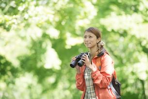 双眼鏡を持ち微笑む女性の写真素材 [FYI04548387]