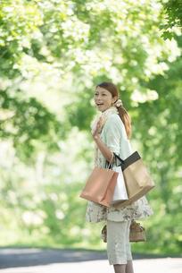 ショッピングバッグを持ち微笑む女性の写真素材 [FYI04548416]