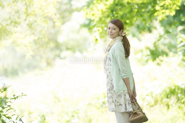 新緑の中で微笑む女性の写真素材 [FYI04548424]