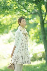 新緑の中で微笑む女性の写真素材 [FYI04548435]