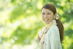 新緑の中で微笑む女性の写真素材 [FYI04548438]