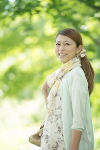 新緑の中で微笑む女性の写真素材 [FYI04548442]