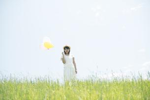 草原で風船を持ち微笑む女性の写真素材 [FYI04548474]