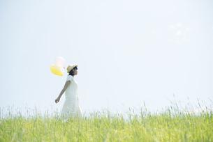草原で風船を持ち微笑む女性の写真素材 [FYI04548475]