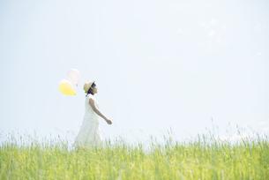 草原で風船を持ち微笑む女性の写真素材 [FYI04548478]