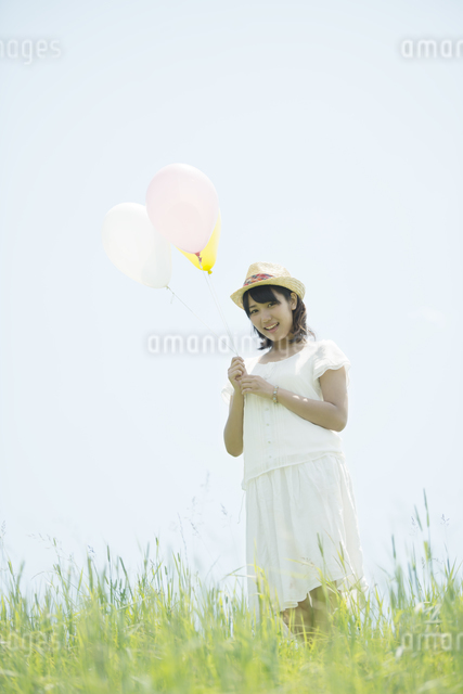草原で風船を持ち微笑む女性の写真素材 [FYI04548480]