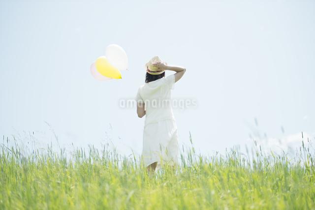 草原で風船を持つ女性の後姿の写真素材 [FYI04548481]