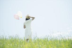 草原で風船を持つ女性の後姿の写真素材 [FYI04548483]