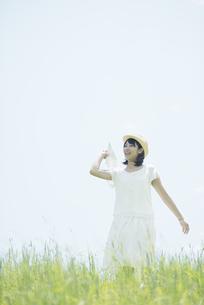 草原で紙飛行機を飛ばす女性の写真素材 [FYI04548486]
