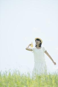 草原で紙飛行機を飛ばす女性の写真素材 [FYI04548489]