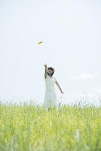 草原で紙飛行機を飛ばす女性の写真素材 [FYI04548491]