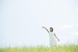 草原で紙飛行機を飛ばす女性の写真素材 [FYI04548494]