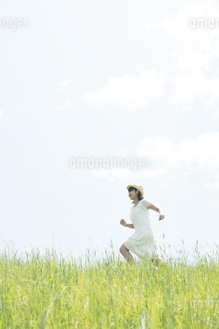 草原を走る女性の写真素材 [FYI04548499]