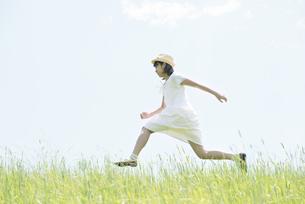 草原を走る女性の写真素材 [FYI04548504]