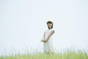 草原で野花を持ち微笑む女性の写真素材 [FYI04548505]