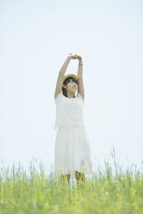 草原で伸びをする女性の写真素材 [FYI04548518]