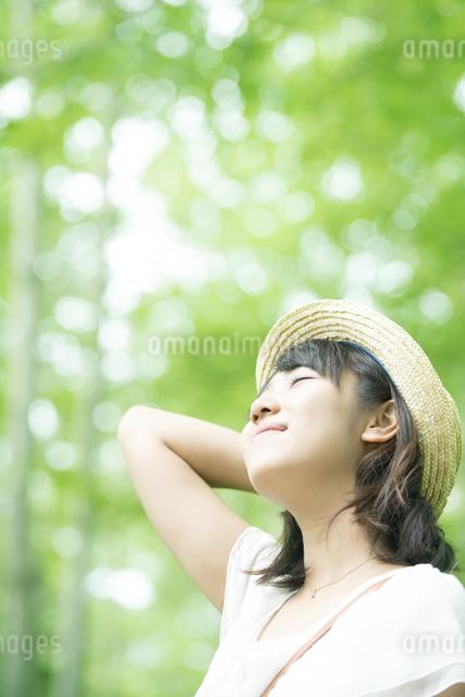 森林の中で目を閉じる女性の写真素材 [FYI04548570]