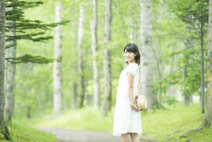 森林の中で帽子を持ち微笑む女性の写真素材 [FYI04548576]